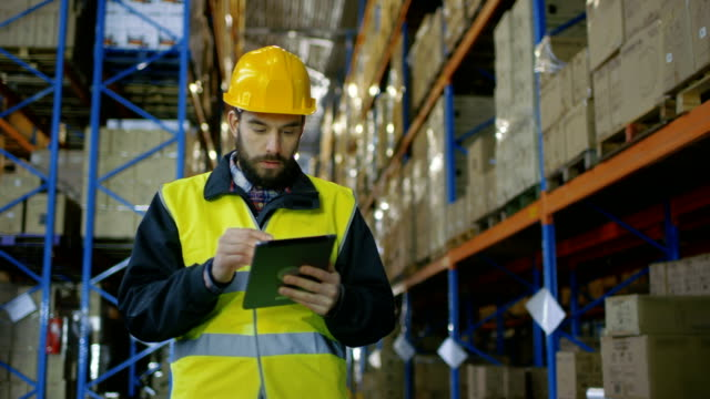 Surveyor Wearing Hard Hat Holds Tablet Computer Counts Merchandise in Warehouse. He Walks Through Rows of Rack Pallets video