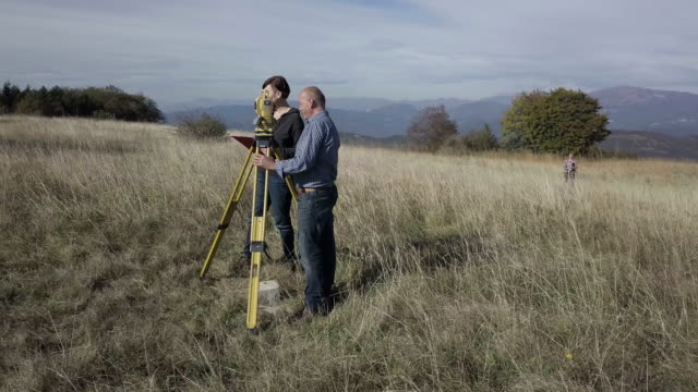 Surveyors Measuring on Top of a Hill Surveyors Measuring on Top of a Hill. survey stock videos & royalty-free footage