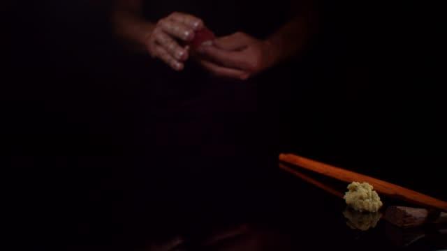 sushi wird in einer dunklen minimalistischen studioszene mit händen und essstäbchen serviert - scheibe portion stock-videos und b-roll-filmmaterial