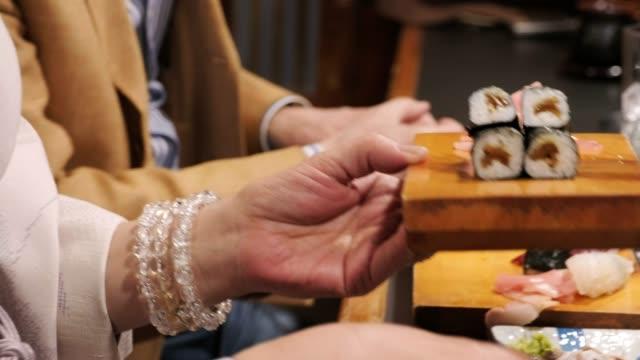 sushi-chef in kleinem tokyo restaurant - sushi stock-videos und b-roll-filmmaterial
