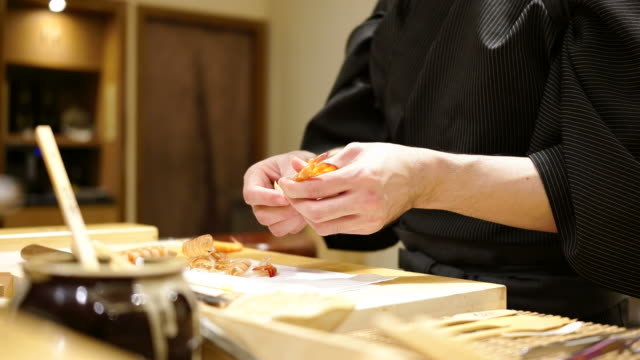 A sushi chef prepares sushi and serves a customer in a small Japanese restaurant, omagase course
