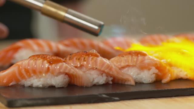 sushi flambieren in zeitlupe - sushi stock-videos und b-roll-filmmaterial
