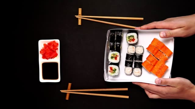 sushi, maki rolls. on plate over black background with space for your text. top view flat lay - food delivery стоковые видео и кадры b-roll