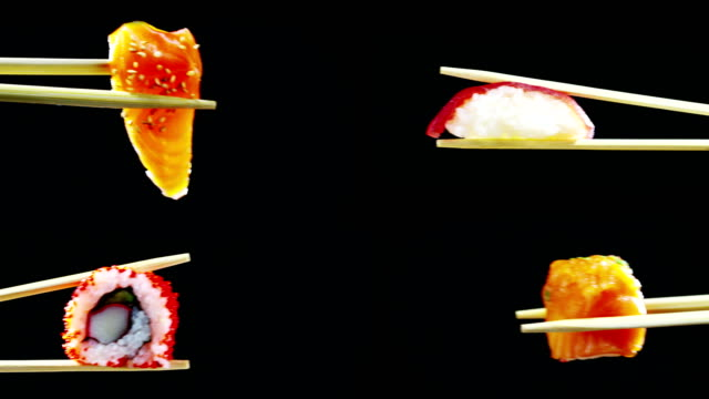 vídeos y material grabado en eventos de stock de sushi calidad alta se convierte en un fondo negro y muestra toda su bondad, alimentos dietéticos y saludables, sabor salado, el sushi es bien con salmón o atún, es una típica comida japonesa - sushi