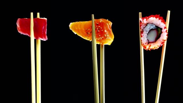 sushi qualität hoch auf einem schwarzen hintergrund und zeigt alle seine güte, diät und gesunde ernährung, herzhaften geschmack, das sushi ist gut mit lachs oder thunfisch, ist ein typisches japanisches essen - sushi stock-videos und b-roll-filmmaterial