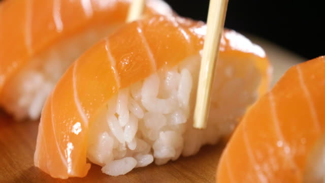 sushi quality high turns on a black background and shows all its goodness, dietary and healthy food, savory flavor, the sushi is well with salmon or tuna, is a typical japanese food - japanese food stock videos and b-roll footage