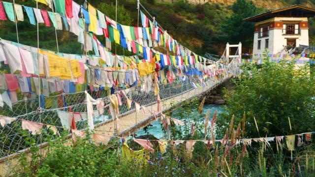 Suspension bridge near Paro, Bhutan Suspension bridge covered in prayer flags near Paro, Bhutan buddhism stock videos & royalty-free footage