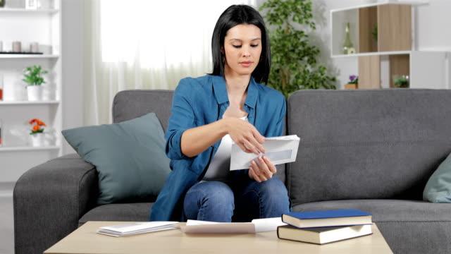 vídeos de stock, filmes e b-roll de mulher suspeita que lê um recibo em casa - e mail