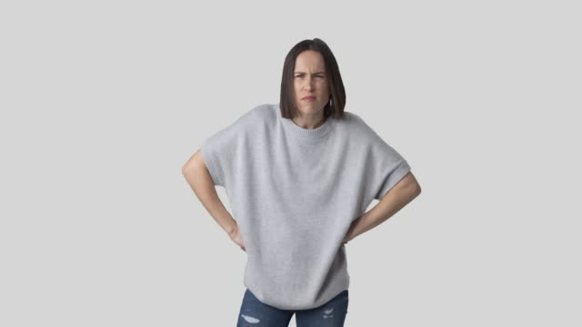 Suspicious woman showing disapproval Suspicious looking woman showing disapproval against white background arms akimbo stock videos & royalty-free footage