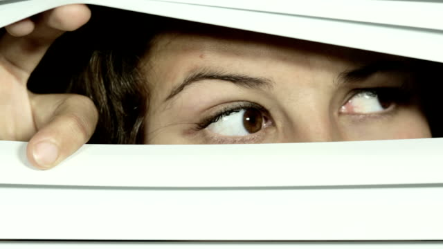 Suspicious young woman opening Venetian blinds a little, then looking carefully all around, suspicious and nervous. video
