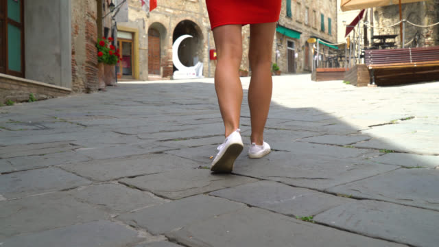 vídeos de stock e filmes b-roll de suvereto, tuscany, italy. girl in red dress walking down the city street close up - saia