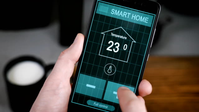 Svart House. Remote home control system on a digital tablet or phone. Men's hands hold a smartphone with an active application for managing the house video