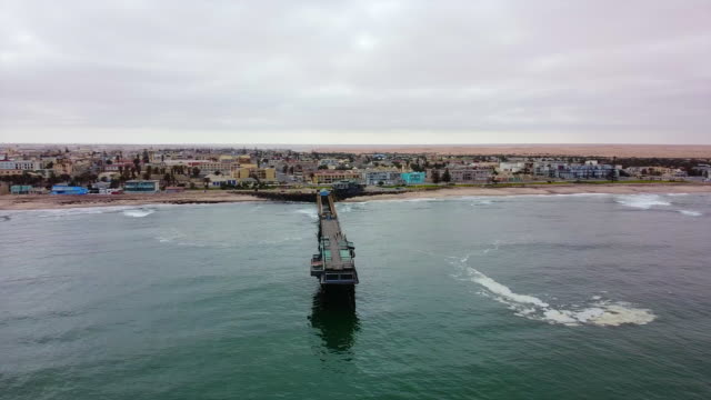 Swakopmund Jetty - Arc a Slow Arc from right to left of the Swakopmund Jetty with the town visible in the background. The sea is very calm and has a slight green color. Skeleton Coast. Namibia. swakopmund stock videos & royalty-free footage