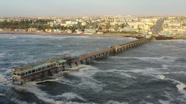 Swakopmund Jetty South Atlantic Ocean 4K Video Aerial View Namibia Aerial 4K Drone Video towards the famous Swakopmund Jetty Bridge - Pier of Swakopmund over the South Atlantic Ocean and Coastline Beach. Aerial Drone Point of View 4K Video, South Atlantic Ocean, Swakopmund, Erongo Region, Namibia, Africa swakopmund stock videos & royalty-free footage