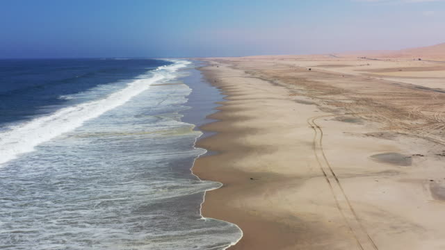 Swakopmund Langstrand Beach Walvis Bay Namibia Drone Video Flight II Langstrand Beach Aerial Drone 4K Video Real Time Flight along the Atlantic Ocean Sea and Sand Coast between Swakopmund and Walvis Bay. Long South Atlantic Ocean Beach Coast - Skeleton Coast of Namibia at Swakopmund with Skid Marks from 4x4 Cars . National Road B2 with Trucks and Cars driving in the background horizon. Skeleton Coast, Swakopmund - Walvis Bay, Erongo Region, Namibia, Africa. swakopmund stock videos & royalty-free footage