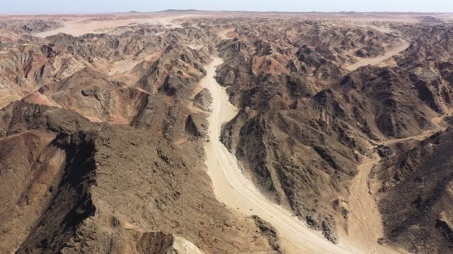 Swakopmund Moon Landscape Namibia Aerial 4K Video Moonscape Canyon Aerial Drone 4K Video flying over rural desert gravel road through the surreal Moon Landscape, Moonscape. Aerial Drone 4K Video. Moon Landscape, Swakopmund, Erongo Region, Namibia. swakopmund stock videos & royalty-free footage