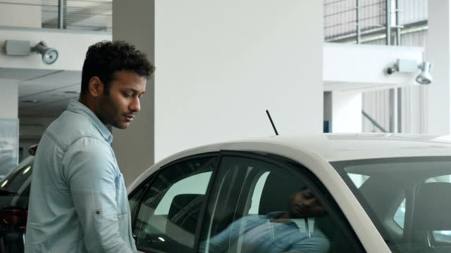 Swarthy man inspecting a salon of a white car video