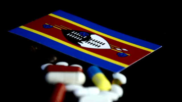 Swaziland flag with lot of medical pills isolated on black background video