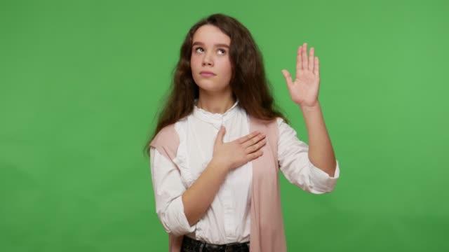 stockvideo's en b-roll-footage met ik zweer! verantwoordelijk oprecht donkerbruin meisje in wit overhemd dat beloftegebaar met hand op hart, eerlijke tiener maakt - swearing