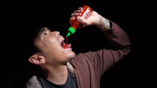 sweaty asian man pouring spicy hot sauce into his mouth against black background - lingua bocca video stock e b–roll