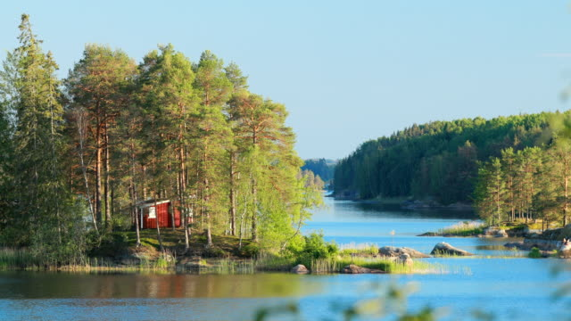 Sweden. Beautiful Red Swedish Wooden Log Cabin House On Rocky Island Coast In Summer Sunny Evening. Lake Or River Landscape