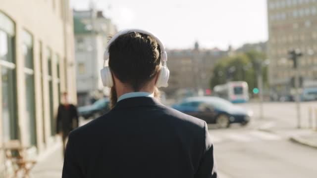 En svensk affärsman går nedför gatan och lyssnar på musik video