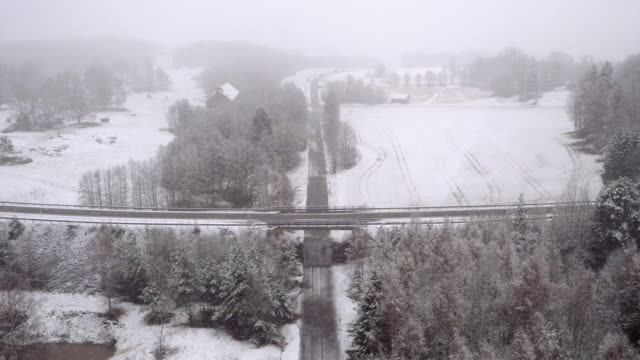 AERIAL: Swedish winter It's snowing, the fields and the trees are covered with snow. A green bus is crossing a bridge. vinter stock videos & royalty-free footage