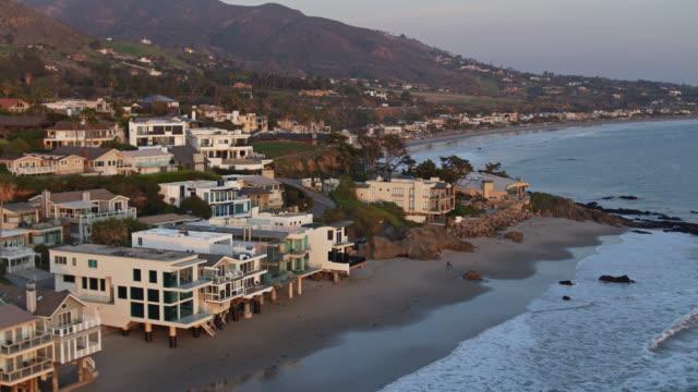 vídeos de stock e filmes b-roll de sweeping drone flight around lechuza point in malibu, california - estrada 001