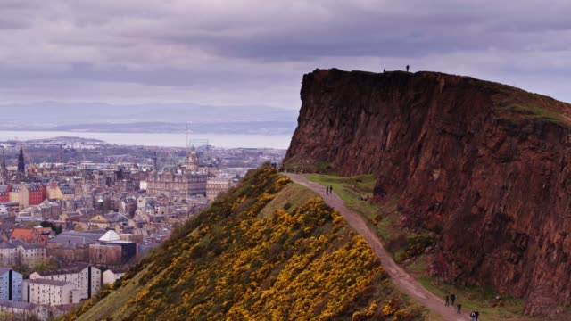 Sweeping Drone Shot Around Salisbury Crags, Edinburgh Aerial shot of the Edinburgh, the capital of Scotland, looking past Salisbury Crags in Holyrood Park to the centre of the city. scotland stock videos & royalty-free footage