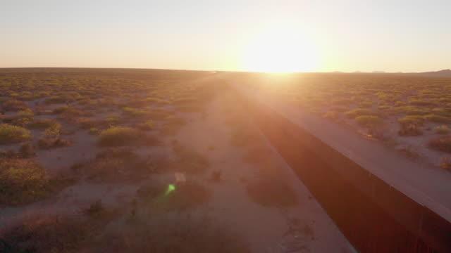 エルパソ、テキサス州、米国とシウダーフアレス、メキシコを分割国境の壁のスイープドローンビュー - 壁点の映像素材/bロール