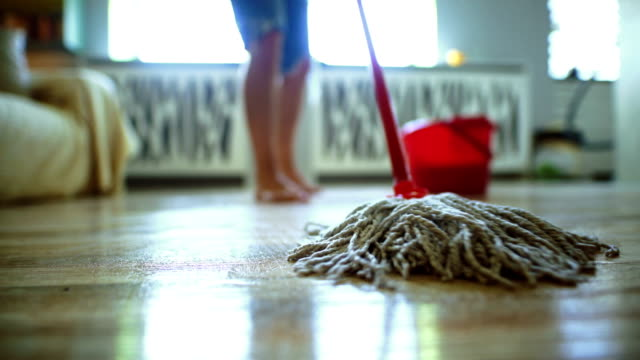 Sweeping the floor with a mop. Closeup low angle view of unrecognizable person mopping a hardwood floor. Very shallow focus. cleaning stock videos & royalty-free footage