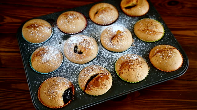 vídeos de stock e filmes b-roll de sweet baked muffins with fruit filling in icing sugar - top view, dark wood table, empty