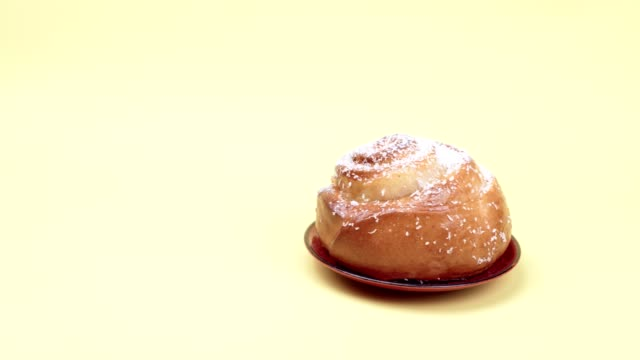 sweet bun on a saucer on a yellow background. - piattino video stock e b–roll