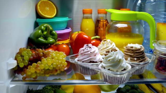 Sweet cakes in the open refrigerator. video