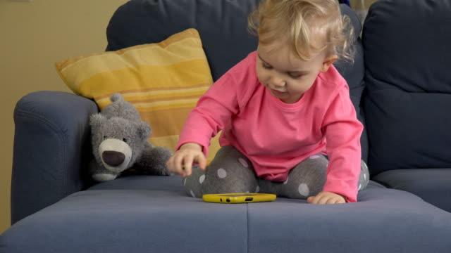 söt kaukasiska barnflicka leker med smartphone ensam på blå soffa. - blue yellow bildbanksvideor och videomaterial från bakom kulisserna