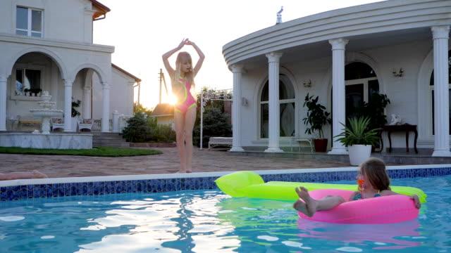 インフレータブルの甘い子がダンス スイミング プールで水着少女日光の下でプールで泳ぐ - 姉妹点の映像素材/bロール