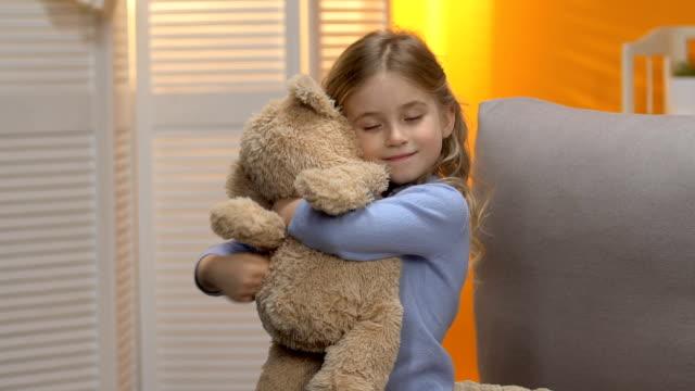 vídeos de stock e filmes b-roll de sweet curly preschool girl hugging teddy bear and smiling, happy childhood - teddy bear