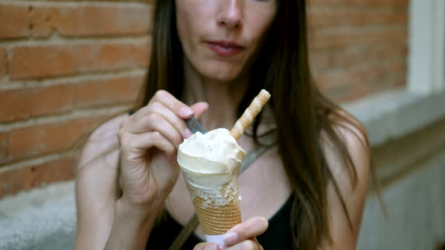 Sweet dessert. Adorable beautiful Caucasian young woman eating delicious ice-cream during her walk in the city Madrid on sunny summer day. Spain. 4K