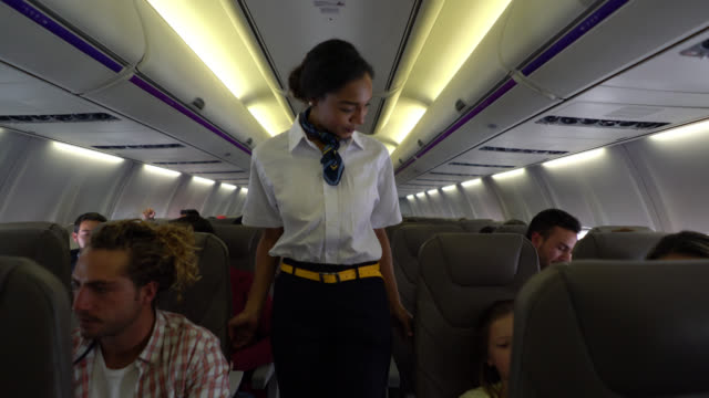 Sweet flight attendant checking if everyone is wearing their seatbelts and helping a little boy