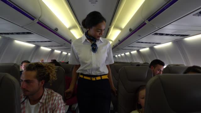 süße flugbegleiterin überprüfen, ob alle ihre sicherheitsgurte tragen und helfen, einen kleiner junge - innerhalb stock-videos und b-roll-filmmaterial