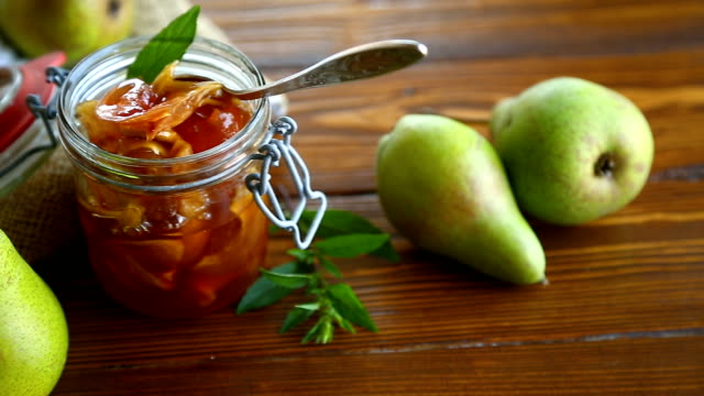 sweet fruit jam with apples and pears in a glass jar sweet fruit jam with apples and pears in a glass jar on a wooden table pear stock videos & royalty-free footage