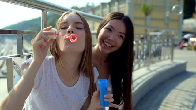 Sweet girl blowing beautiful bubbles in the air video