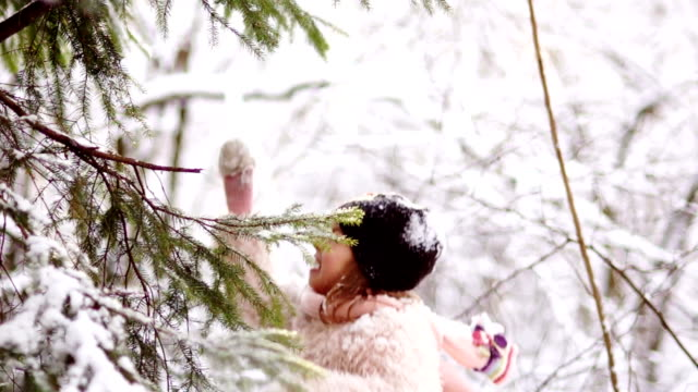 a sweet girl shakes snow from the branches of winter trees. winter games, happy holidays, christmas holidays. pink mittens and scarf - happy holidays stock videos & royalty-free footage