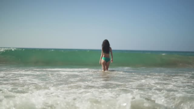 Sweet girl with a gorgeous figure standing in the background of foam splash of sea wave. Young girl with perfect body walks into the sea and turns to the camera. Slow motion.