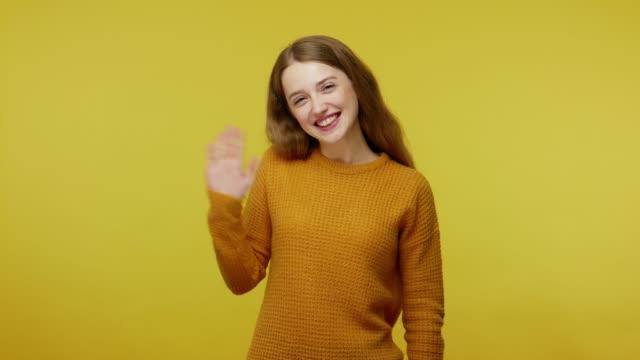 vídeos y material grabado en eventos de stock de dulce saludo de mujer, hospitalidad. amigable sociable hermosa chica con el pelo castaño en jersey agitando la mano gesturing hi - chica adolescente