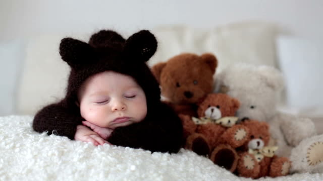 sweet little baby boy, dressed in handmade knitted brown soft teddy bear overall, sleeping cozy at home in sunny bedroom with lots of teddy bears around him - abbigliamento da neonato video stock e b–roll