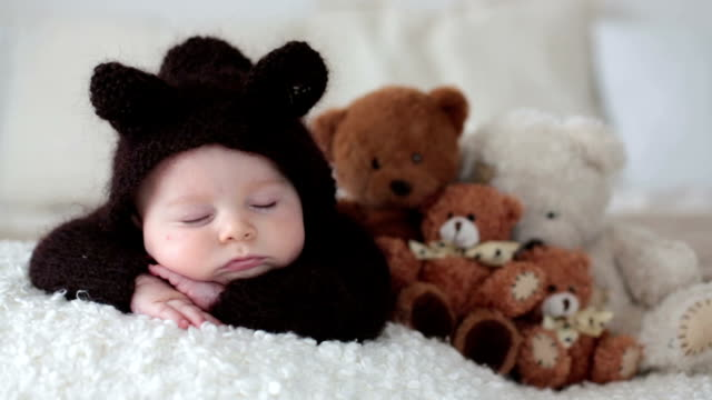 Sweet little baby boy, dressed in handmade knitted brown soft teddy bear overall, sleeping cozy at home in sunny bedroom with lots of teddy bears around him video