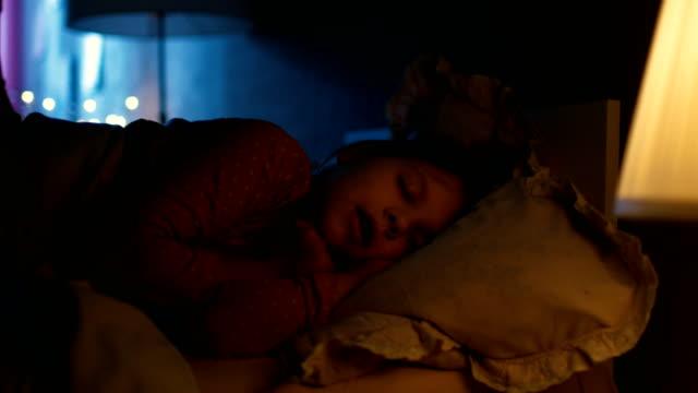 Sweet Little Girl Sleeps in Her Bed at Night, Her Mother Tucks Her Blanket in. video