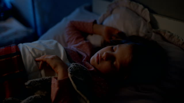 sweet little girl sleeps in her bed while hugging her plush toys. - solo una bambina femmina video stock e b–roll