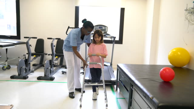 sweet little girl using a mobility walker with there help of therapist during physical therapy - fisioterapia video stock e b–roll